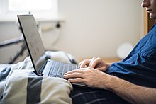 Working from Bed - A Man Works from Home with a Laptop in Bed.jpg
