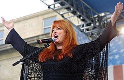 A woman with long red hair wearing black, singing into a microphone while raising both her arms