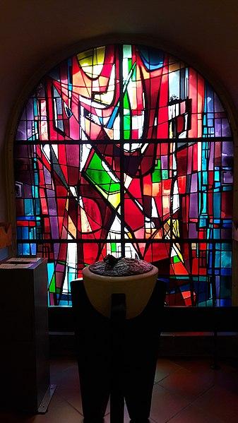 Abstrakt Kierchefënster vum Gustave Zanter an der Kierch vun Ëlwen, 1969. Dës Fënster ersetzt dat fréiert Agangsportal.