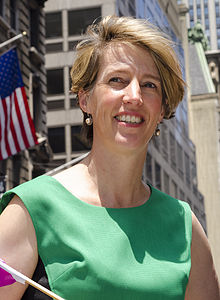 Woman with short brown hair and green sleeveless dress smiling into camera with United States flag in left background