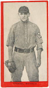 a young man in an old-style baseball uniform wears a glove and stares at the camera