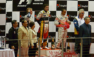 Renault Formula One crash controversy - Alonso on the podium of the 2008 Singapore Grand Prix, with Briatore far right (white shirt)
