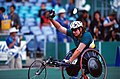 281000 - Athletics wheelchair racing Louise Sauvage waves - 2000 Sydney race photo.jpg