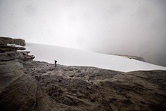 Sierra Nevada del Cocuy - A hiker reaches the glacier atop Ritak U'wa Blanco in Sierra Nevada de Cocuy National Park, part of the Cordillera Oriental of the Colombian Andes.
