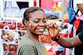 A lady painting and decorating her face during Chale Wote Street Art Festival.jpg