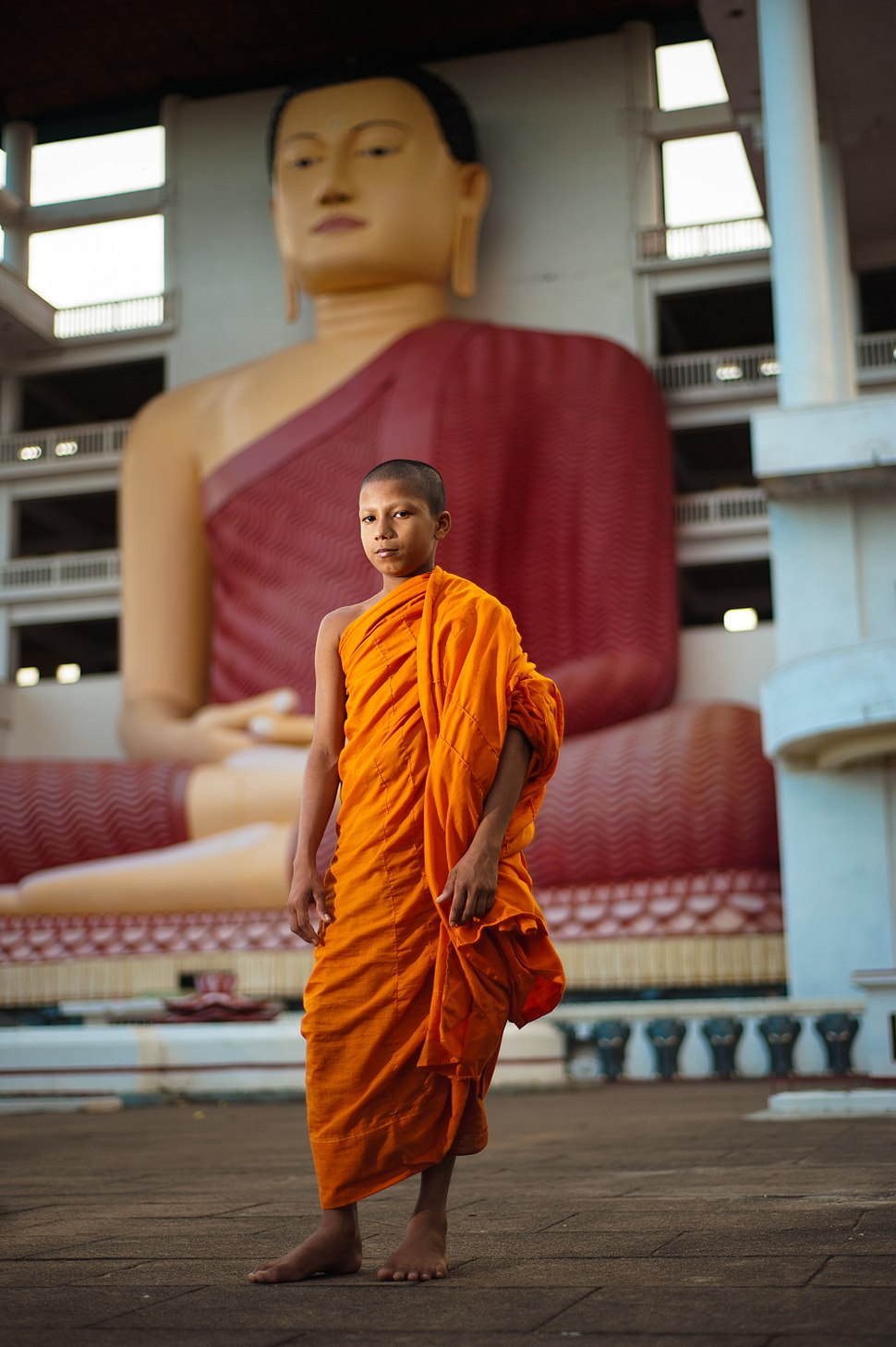 A young monk against the background of Big Buddha statue in Weherahena Temple. Matara, Southern Province, Sri Lanka