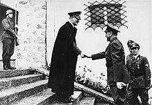 Photo noir et blanc, prise le 9 juin 1941 à Berchtesgaden, en Allemagne. Au centre de la photo, Adolf Hitler, portant un long manteau noir et une casquette militaire, sert la main d'Ante Pavelić (à droite), dirigeant de l'État indépendant de Croatie. Les deux hommes sont de profil, debout, sur les marches de l'escalier menant à l'entrée de la résidence secondaire de Hitler. Un soldat en arme se tient debout, en haut de l'escalier (en haut à gauche de la photo). Au second plan, deux officiers allemands (en bas à droite de la photo) assistent à la scène. L'arrière-plan de la photo est constitué d'un mur blanc percé d'une fenêtre grillagée (au-dessus de la tête du dirigeant croate).