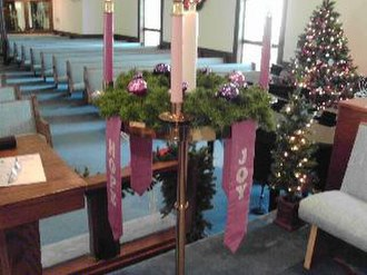 Gaudete Sunday - One of the candles surrounding the Christ Candle in the Advent wreath is rose coloured, for Gaudete Sunday or Joy Sunday, the beginning of the third week in Advent. The parament next to this rose coloured candle has the word Joy printed on it.