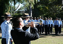 Photograph of a trumpeter in the foreground, with uniformed Air Force Cadets in the background, on the St John's site