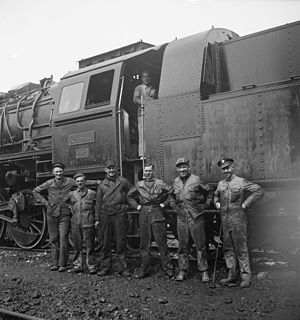 Islamic Republic of Iran Railways - Following the Anglo-Soviet invasion of Iran, American and British railroad crews pose alongside a locomotive, ca. 1943