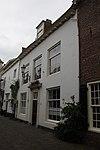 foto van Huis met gepleisterde gevel met rechte kroonlijst. Omlijste voordeur