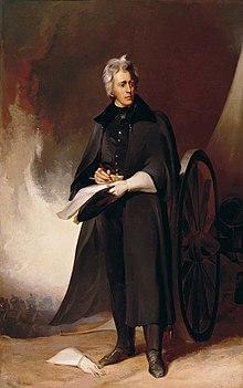 Gråhåret mann i blå hærfrakk og svart frakk har venstre hanske på og høyre hanske på bakken.  Han skriver på papirer og står ved siden av en kanon.