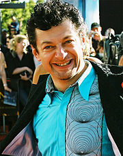A photograph of Andy Serkis, a dark-haired man wearing a blue shirt and a dark blazer.