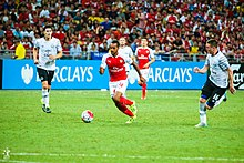 Theo Walcott dribbles past Gareth Barry and James McCarthy at the National Stadium in Singapore.