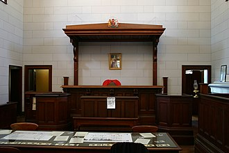 "Bench (law) - A judge's bench in a courtroom in Beechworth, Victoria, Australia. The term ""bench"" is also used as a metonym to mean all the judges of a certain court or members of a judiciary."