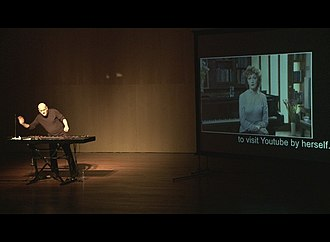 "Avi Benjamin - Avi Benjamin is performing on stage at his show ""Live Soundtracks for Movies That Don't Yet Exist"" at Tel Aviv Museum of Art, March 2012. On the screen – actress Evgenia Dodina"