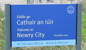 "Place names in Ireland - Welcome sign at Newry - cathair means ""stone ringfort"" but has been adopted as an Irish term for ""city"""
