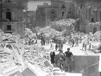 Siege of Malta (World War II) - Service personnel and civilians clear up debris on a heavily bomb-damaged street in Valletta, Malta on 1 May 1942