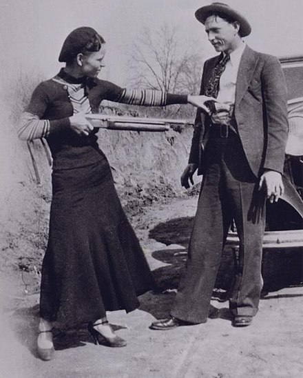 Bonnie with a shotgun reaches for officer Persell's pistol in Clyde's waistband. Bonnie apuntant de broma a Clyde amb una escopeta.jpg