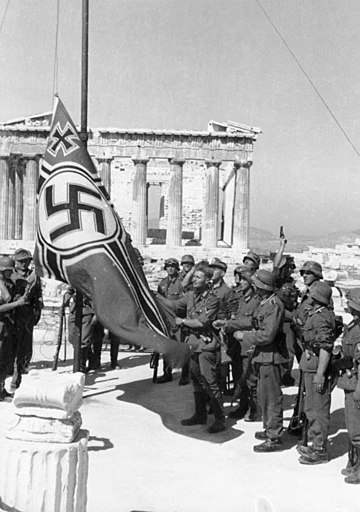 The symbolic beginning of the occupation: German soldiers raising the German War Flag over the Acropolis of Athens. It would be taken down in one of the first acts of resistance by Apostolos Santas and Manolis Glezos. Bundesarchiv Bild 101I-164-0389-23A, Athen, Hissen der Hakenkreuzflagge.jpg