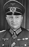 The head of an elderly man, shown from the front. He wears a peaked cap and a military uniform. His facial expression is a determined and confident smile; his eyes looks to the right of the camera.