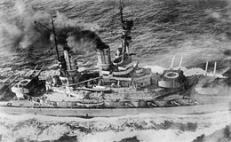 Overhead view of a large battleship; black smoke pours from its smoke stacks as it steams through choppy seas.