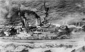 Overhead view of a large battleship; black smoke pours from its smoke stacks as it steams through choppy seas