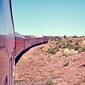 Central Australia Railway -- The Ghan (narrow-gauge) climbing out of the Finke River depression, probably May 1974 (Hugh S Williams).jpg
