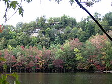 A cliff with a small shelter at its top, viewed from across a lake. The leaves in the trees growing from the slopes are green, pink, purple, and red.