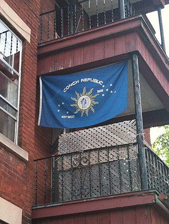 Conch Republic - A Conch Republic flag hanging from a balcony.