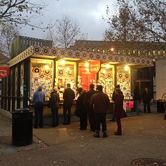 """Conflict Kitchen - After receiving threats Conflict Kitchen temporarily shut down. While closed, supporters covered its exterior with hundreds of hand-written notes of support, such as """"Stay Strong We Support Conflict Kitchen."""" This picture shows the restaurant after it re-opened, with long lines of patrons."""