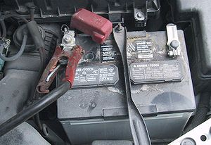 Automotive battery - A positive (red) jumper cable connected to battery post. An optional hydrometer window is visible by the single jumper clamp. (The black negative jumper clamp is not shown.)