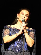 A woman with very long dark hair, wearing a purple and black lace dress, singing into a microphone