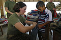 Defense.gov News Photo 110207-M-9683P-197 - U.S. Marine Corps Lance Cpl. Erica R. Steele a field wireman with 3rd Marine Logistics Group fits a student with donated clothes during exercise.jpg