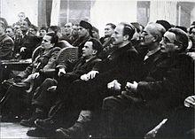 Photograph of a sitting audience looking at a point off-camera