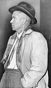 A black and white photograph of a man in late middle-age wearing a dark cowboy hat, white shirt, tie, gray jacket, scarf and gray trousers. He faces left and his left hand is in his trouser pocket.