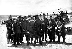 Nine men wearing a mixture of military uniforms with caps and flying suits with goggles, in front of a row of military biplanes