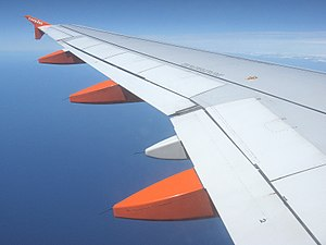 Flap (aeronautics) - The three orange pods are fairings streamlining the flap track mechanisms. The flaps (two on each side, on the Airbus A319) lie directly above these.
