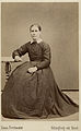 En kvinna poserar i en lång klänning - Nordiska Museet - NMA.0039779.jpg