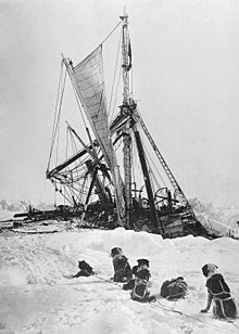 Side of a wooden steamship held in solid ice, leaning heavily to the left with a lfeboat swinging in its davits. One man visible on the ice, another aboard the ship, looking down.