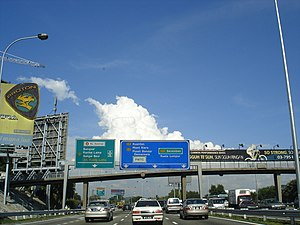 Road signs in Malaysia - Malaysian road signs at Federal Highway in Petaling Jaya. On the left side is the toll expressway and the highway's green signs and on the right side is the non-tolled federal, state and municipal highway's blue signs.