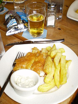 A traditional English meal of fish and chips, ...