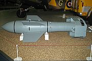 A grey missile sitting on a light-colored floor