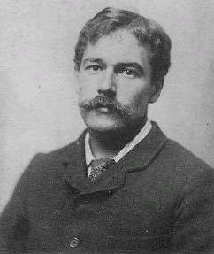 A bust-length monochrome photograph of a white male with a handlebar moustache; wearing a jacket and tie.