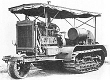 An early bulldozer-like tractor, on crawler tracks, with a leading single wheel for steering - projecting from the front -  on an extension to the frame. The large internal combustion engine is in full view, with the cooling radiator prominent at the front. An overall roof is supported by thin rods, and side protection sheeting is rolled up under the edge of the roof.