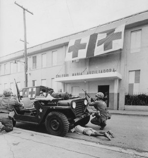 Humanitarian G.I.'s. Firefight where G.I. pushes little kid under jeep for protection, Santo Domingo, May 5., 1965 - NARA - 541806 (cropped).tif
