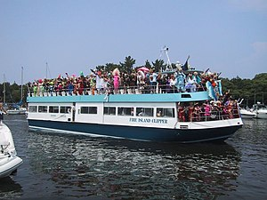 Fire Island Pines, New York - A ferry with drag queens during the Invasion of the Pines arrives at Pines Harbor