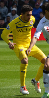 Jem Karacan, wearing Reading's 2012–13 away kit, contests with Bryan Ruiz for the ball