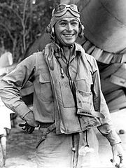 A young-looking man in pilot gear standing in front og a group of trees.