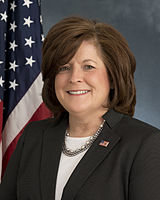 A portrait photo of Julia Pierson in front of a US flag